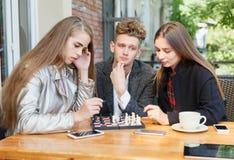Knappe kerel en slimme meisjesvrienden die schaak op een koffieachtergrond spelen Het concept van intelligentiespelen royalty-vrije stock afbeeldingen