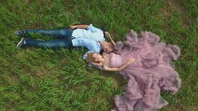 Knappe kerel met meisje het liggen op het gebied en het dromen stock video