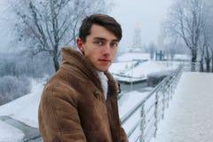 Knappe kerel op de brug tijdens de winter royalty-vrije stock fotografie