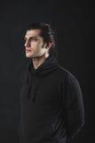 Knappe kerel op donkere achtergrond in studio Stock Afbeelding