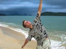 Knappe kerel op een exotisch strand gang op het strand vóór tropische regen Actuele eilanden stock foto's