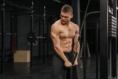 Knappe kerel opleidingstriceps die in gymnastiek omhoog lichaams bodybuilding atleet pompen stock foto's