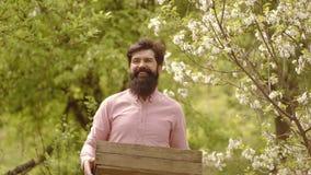 Knappe landbouwersmens in openlucht in bloeiende bomen De lente of zomer voor de gebaarde mens op de boerderij Landbouwersconcept stock videobeelden