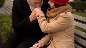 Knappe man het kussen hand van zijn vrouw, mooi paar op bank, de herfstpark stock foto