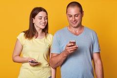 Knappe man met mobiele in hand telefoon, controlerend zijn sociaal netwerk, tribunes dichtbij leuke speelse donkerbruine vrouw di royalty-vrije stock afbeelding
