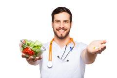 Knappe mannelijke arts die salade en pillen tonen stock afbeeldingen