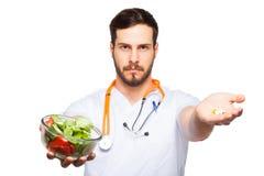 Knappe mannelijke arts die salade en pillen tonen stock fotografie