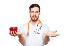 Knappe mannelijke arts die salade en pillen tonen royalty-vrije stock afbeelding
