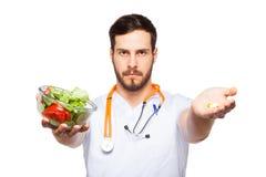 Knappe mannelijke arts die salade en pillen tonen stock foto's