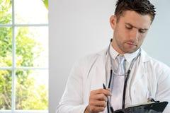 Knappe mannelijke arts, gp, met stethoscoop en klembord royalty-vrije stock afbeeldingen