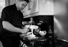 Knappe mannelijke chef-kok die bovenmatig gebakje afsnijden van schotel royalty-vrije stock afbeeldingen