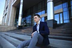 Knappe mannelijke directeurzitting op treden buiten een gebouw stock afbeeldingen