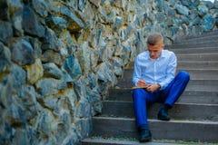 Knappe mannelijke directeurzitting op treden buiten het maken van zijn plannen stock foto