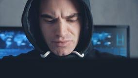 Knappe Mannelijke hakker in kap die aan een computer in datacentrum werken stock video
