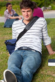 Knappe mannelijke student die op gras met zijn zak ligt Stock Afbeelding