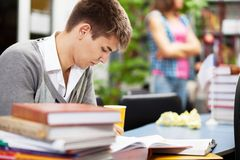 Knappe mannelijke student in een bibliotheek Royalty-vrije Stock Afbeelding