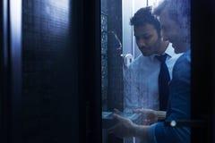Knappe mannelijke technici die in de serverruimte werken royalty-vrije stock afbeelding