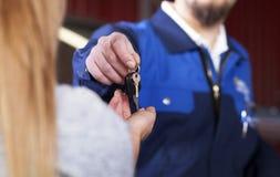 Knappe mecanic auto teruggevend de sleutels Royalty-vrije Stock Fotografie