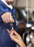 Knappe mecanic auto teruggevend de sleutels Stock Fotografie