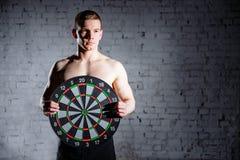Knappe mens in de gymnastiek die een dartboarddoel houden Het concept succes en voltooiing van doelstellingen, resultaten royalty-vrije stock afbeeldingen