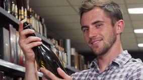 Knappe mens die aan de de wijnfles van de cameraholding glimlachen stock video