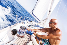 Knappe mens die aan zeilboot werken stock foto's