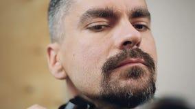 Knappe mens die aandachtig zijn baard verzorgen, die op een eerste datum voorbereidingen treffen te gaan stock videobeelden