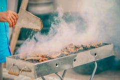 Knappe mens die barbecue voor vrienden voorbereiden Hand van de hogere mens die wat vlees roosteren stock afbeelding
