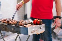 Knappe mens die barbecue voor vrienden voorbereiden Hand van de jonge mens die ??n of andere vlees en groente roosteren stock foto's
