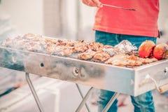 Knappe mens die barbecue voor vrienden voorbereiden Hand van de jonge mens die ??n of andere vlees en groente roosteren stock afbeelding