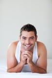 Knappe mens die in bed het glimlachen ligt Stock Foto