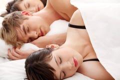 Knappe mens die in bed met twee meisjes ligt Royalty-vrije Stock Afbeeldingen