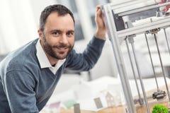 Knappe mens die bij 3D printer en het glimlachen leunen Royalty-vrije Stock Foto