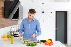 Knappe mens die in blauw overhemd groenten voor salade mengen Stock Foto's