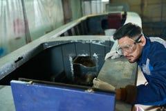 Knappe mens die boot in workshop herstellen stock fotografie
