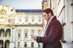 Knappe in mens die celtelefoon met behulp van aan typetekst Stock Fotografie