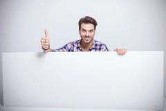 Knappe mens die de duimen op gebaar tonen Stock Afbeelding