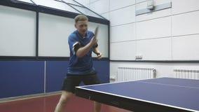 Knappe mens die de pingpong spelen bij het hof stock videobeelden