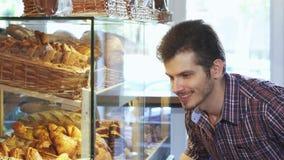 Knappe mens die desserts kiezen van de showcase bij de bakkerij stock videobeelden