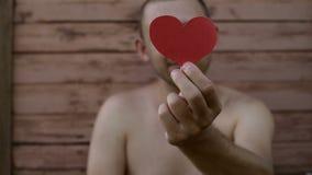 Knappe mens die een document hart houden stock videobeelden
