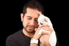 Knappe mens die een hond Chihuahua houdt Stock Foto