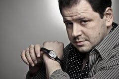 Knappe mens die een horloge opstijgt. Royalty-vrije Stock Foto