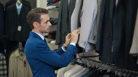 Knappe Mens die een kostuum kiezen bij kledingsopslag stock video