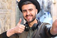 In knappe mens die een selfie en geven omhoog in openlucht nemen duimen stock afbeeldingen