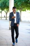 Knappe mens die en tekstbericht op cellphone lopen verzenden Stock Fotografie