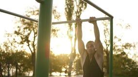 Knappe mens die gymnastiek hebben die op rekstok in openlucht opleiden Doet gymnastiek- stunts op de dwarsbalk in het park stock videobeelden