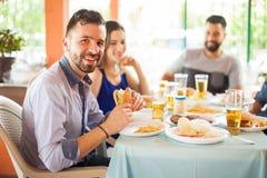 Knappe mens die hamburger met vrienden eten Stock Foto