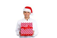 Knappe mens die Kerstmanhoed dragen en een heden houden royalty-vrije stock foto