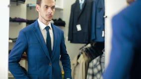 Knappe Mens die kostuum dragen bij kledingsopslag stock footage