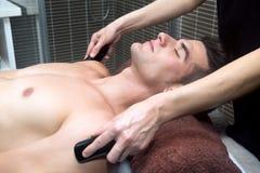 Knappe mens die massage met hete stenen krijgen Royalty-vrije Stock Afbeeldingen